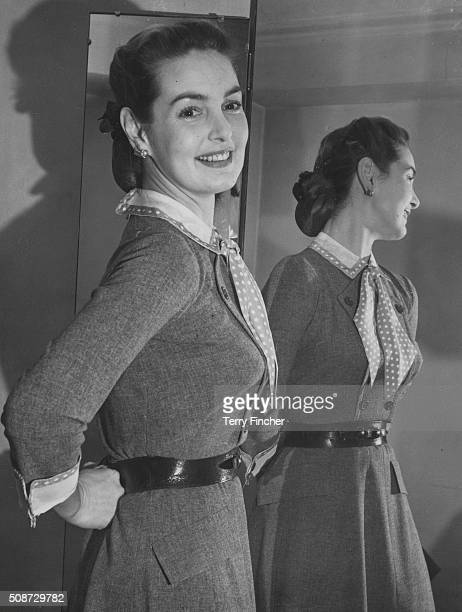 Portrait of actress Patricia Roc standing in front of a mirror wearing a grey day dress as she tries on outfits for her role in the film 'Something...