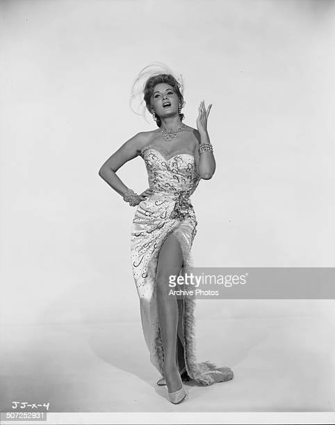 Portrait of actress Rhonda Fleming wearing an evening dress with a thighhigh split as she appears in the movie 'Alias Jesse James' 1959