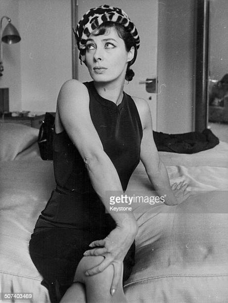 Portrait of actress Rita Gam wearing a leopard print hat and sitting on a bed during a visit to London September 13th 1960