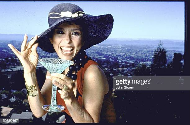 Portrait of actress Rita Moreno at home holding a martini glass.
