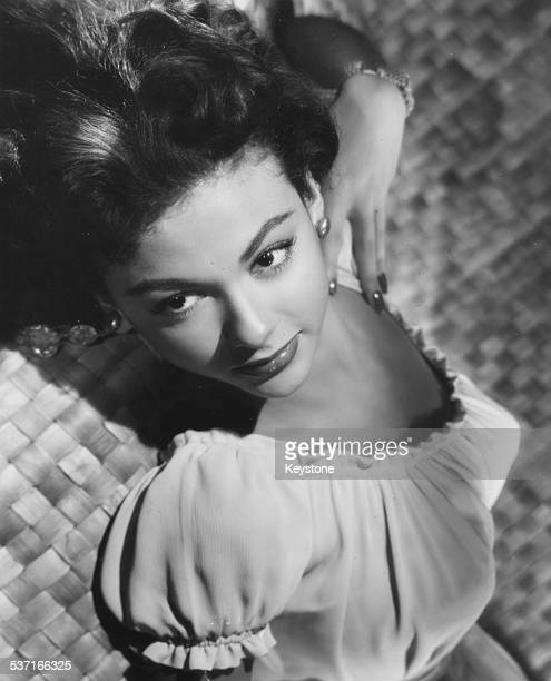 Portrait of actress Rita Moreno reclining backwards, as she appears in the movie 'Cattle Town', 1952.