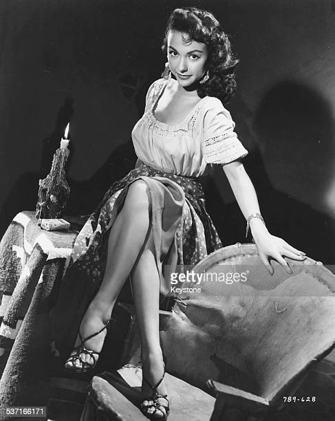 Portrait of actress Rita Moreno, sitting on a table with her feet on a chair, as she appears in the movie 'Cattle Town', 1952.