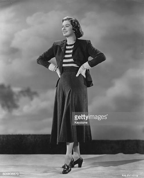 Portrait of actress Rosalind Russell wearing a midiskirt suit and striped blouse circa 1940