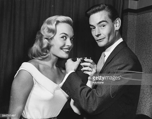 Portrait of actress Shirley Eaton and her husband Colin LentonRowe drinking from each other glasses as they celebrate their engagement Kenton England...