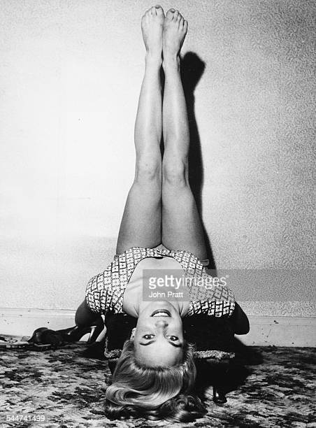 Portrait of actress Shirley Eaton reclining backwards with her legs in the air circa 1955