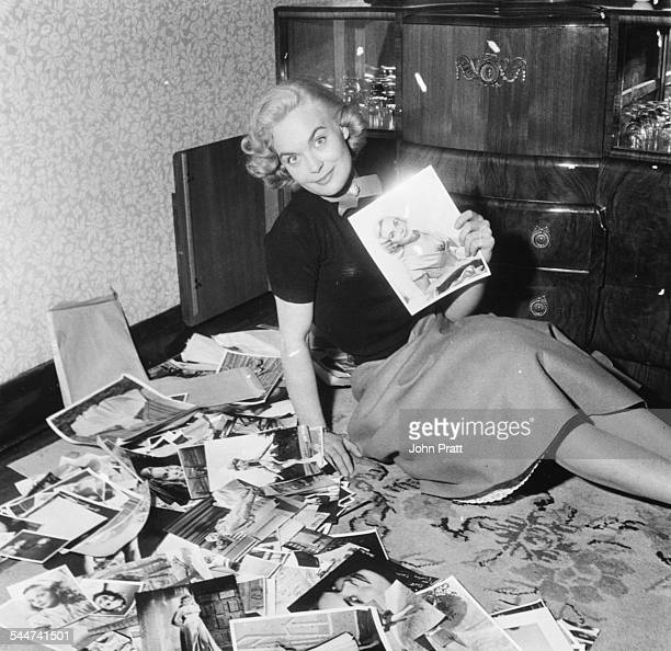 Portrait of actress Shirley Eaton sitting on the floor of her home surrounded by all of her head shots circa 1955