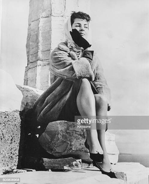 Portrait of actress Silvana Pampanini wearing a winter coat and head scarf sitting on a rock outcrop during a visit to Cape Sounion on a sightseeing...