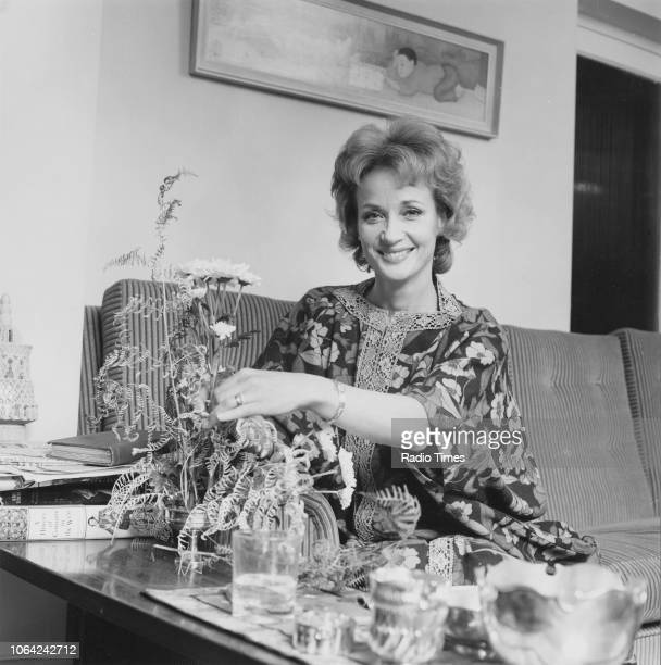 Portrait of actress Sylvia Syms sitting on a sofa and arranging flowers November 1971