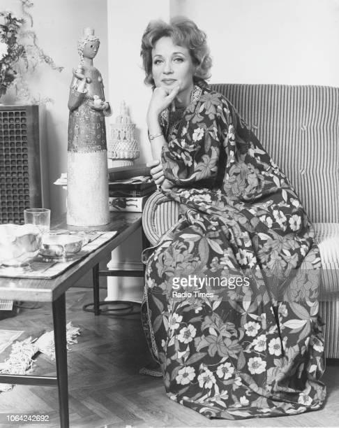 Portrait of actress Sylvia Syms sitting on a sofa November 1971