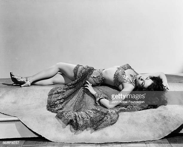 Portrait of actress Yvonne De Carlo wearing a sequin two piece costume and lying back on a rug for Universal Pictures 1945