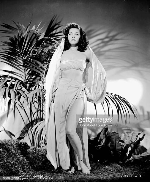 Portrait of actress Yvonne De Carlo wearing a two piece draped outfit in a jungle setting for Paramount Pictures 1942