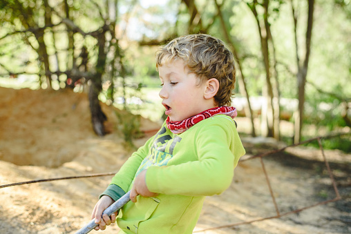 Portrait of adorable 5 year old boy playing freely in nature to improve his motor development .. 1168427481