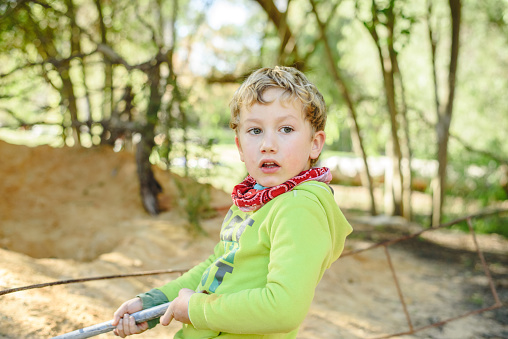 Portrait of adorable 5 year old boy playing freely in nature to improve his motor development .. 1168427486