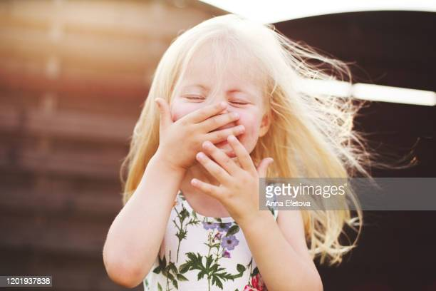 portrait of adorable little blonde girl who is laughing. - small faces stock pictures, royalty-free photos & images