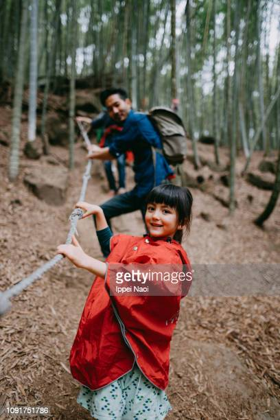 Portrait of adorable mixed race little girl hiking in bamboo grove