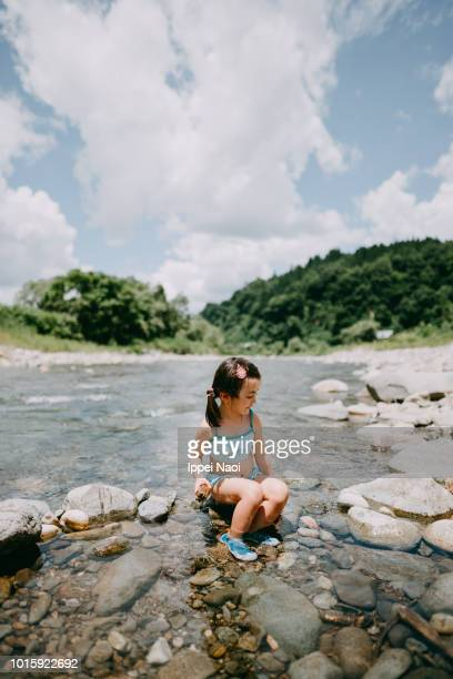Portrait of adorable mixed race little girl playing in river, Niigata, Japan