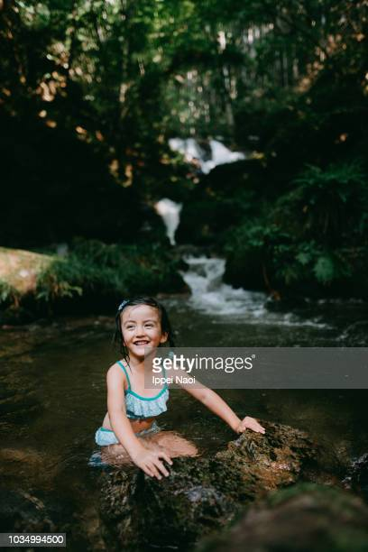 Portrait of adorable mixed race little girl playing in river water in forest