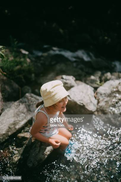 Portrait of adorable mixed race little girl playing in river water