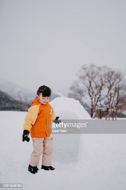 Portrait of adorable mixed race preschool girl in front of igloo