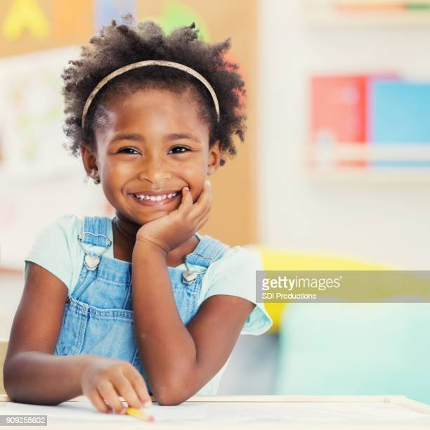 portrait of adorable preschooler in her classroom - children only stock pictures, royalty-free photos & images