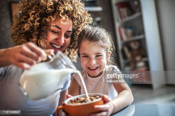 portrait of adorable young girl and mother having breakfast - dairy product stock pictures, royalty-free photos & images