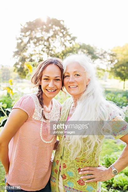 Portrait of adult daughter and mother in garden