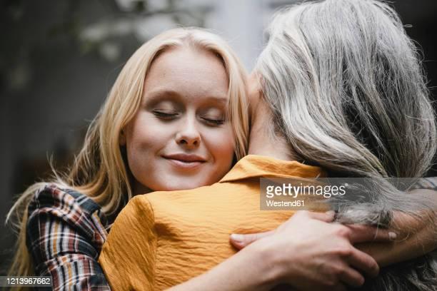 portrait of adult daughter embracing mother outdoors - dankbarkeit stock-fotos und bilder