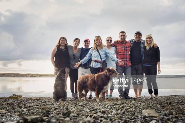 portrait of adult family and dogs on shingle beach, maine, usa - heshphoto stock-fotos und bilder