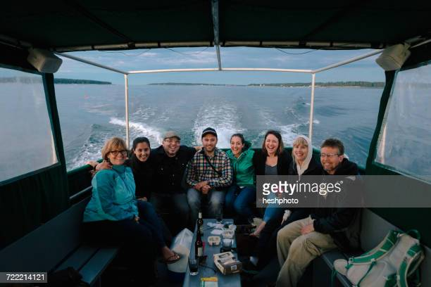 portrait of adult family sitting in boat at sea near coast of maine, usa - heshphoto stockfoto's en -beelden