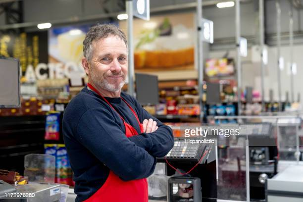 portrait of adult male cashier at the supermarket facing camera smiling with arms crossed - cashier stock pictures, royalty-free photos & images