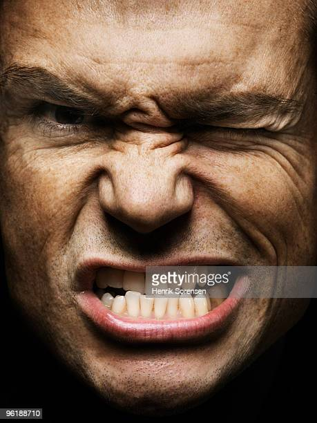portrait of adult male with clinched teeth - clenching teeth stock pictures, royalty-free photos & images