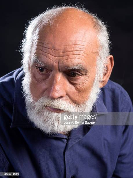 Portrait of adult man of white beard with thoughtful gesture.