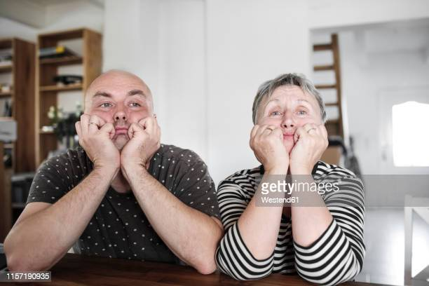 portrait of adult son with senior mother sitting at table at home with head in hands - verveling stockfoto's en -beelden