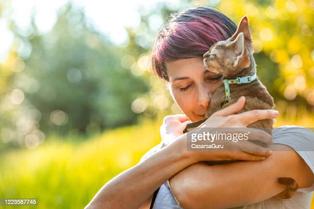 portrait of adult woman with eyes closed hugging her kitten outdoors in nature - stock photo - kitten stock pictures, royalty-free photos & images