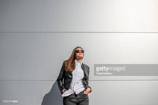 portrait of adult woman with hands in pockets standing outdoors - fotografia de três quartos imagens e fotografias de stock