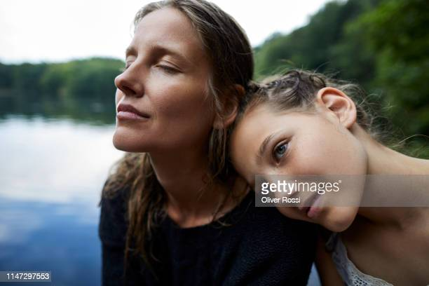 portrait of affectionate mother and daughter at a lake - mid adult women photos et images de collection