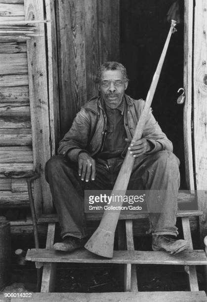 Portrait of African American freedman sitting on doorstep holding horn Texas USA 1930 From the New York Public Library