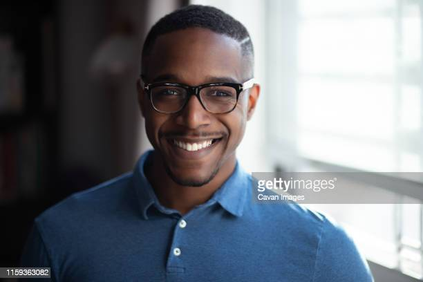 portrait of african american man with glasses looking to camera - polo stock pictures, royalty-free photos & images