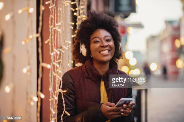 portrait of african american woman listening music - christmas music stock pictures, royalty-free photos & images