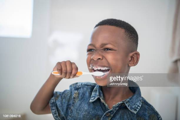 portrait of african boy brushing his teeth - brushing teeth stock pictures, royalty-free photos & images