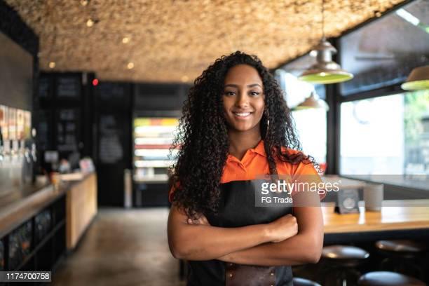 retrato da empregada de mesa/proprietário africanos da etnia no restaurante - pequeno - fotografias e filmes do acervo