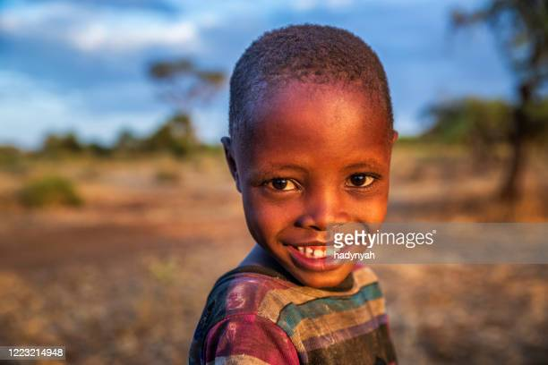 portrait of african little boy from masai tribe playing on savanna, east africa - east african tribe stock pictures, royalty-free photos & images