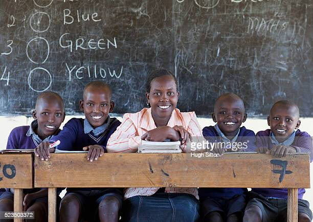 portrait of african schoolboys (10-12) with teacher sitting in front of blackboard - hugh sitton stock pictures, royalty-free photos & images
