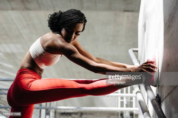 portrait of african sportswoman stretching her leg - warm up exercise stock pictures, royalty-free photos & images