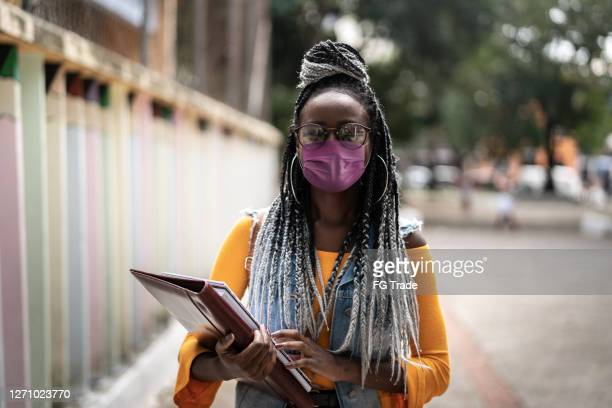 portrait of african student wearing face mask at street - college student stock pictures, royalty-free photos & images