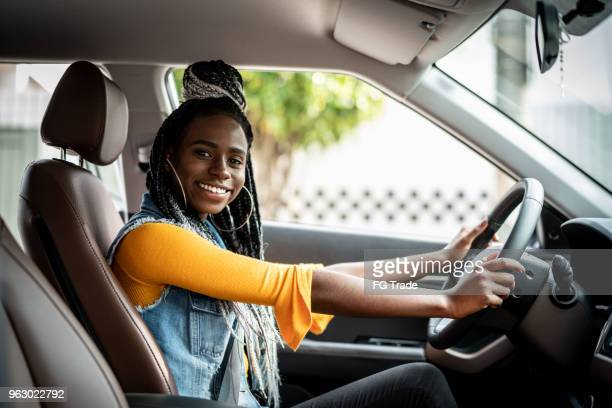 portrait of african woman sitting in car - test drive stock pictures, royalty-free photos & images