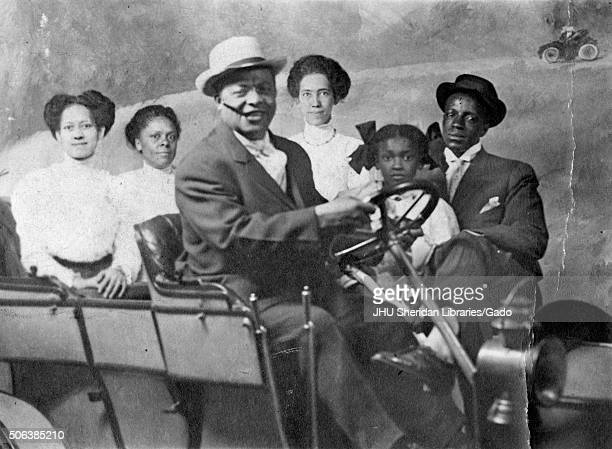 Portrait of AfricanAmerican family with automobile in photographic studio 1930