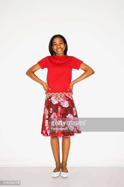 Portrait of African-American teen girl standing with hands on her hips against white background.