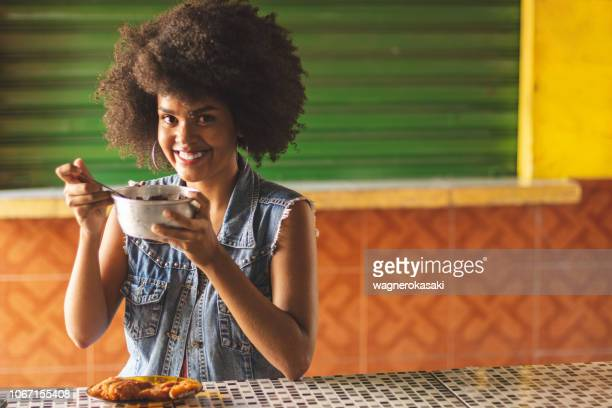 portrait of afro brazilian woman eating fried fish with acai, a typical food combination of amazonian cuisine - acai stock pictures, royalty-free photos & images