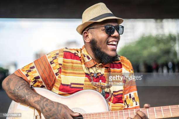portrait of afro descent smiling and playing guitar - musician stock pictures, royalty-free photos & images